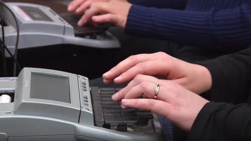 Hands writing on steno keyboard